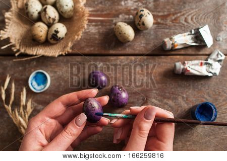 Preparing for Easter holiday flat lay. Top view on hands coloring eggs to purple. Handmade decoration, art, hobby concept