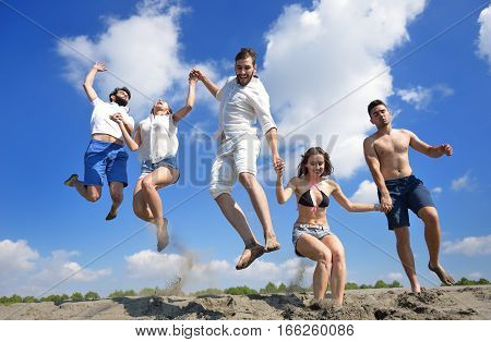 Image of five energetic people jumping at the beach.