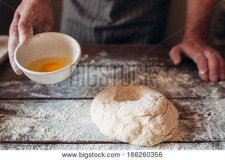 Making dough for bread or pie free space. Baker standing at kitchen table with eggs and raw pastry. Bakery, cooking, hobby concept