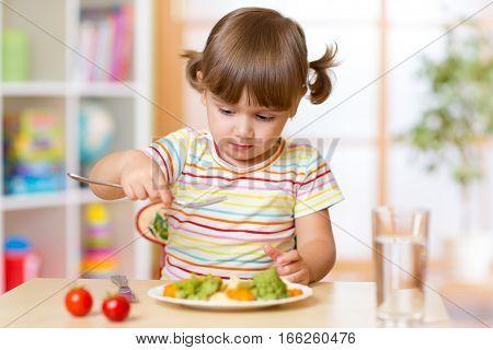 Funny little girl has a lunch in kindergarten