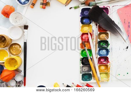 Gouache and watercolor dye palette on white table. Artist workplace with colorful drawing tools, free space. Art, workshop, painting, inspiration, craft, creativity concept