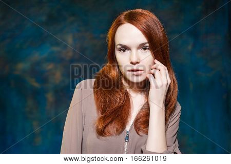 Long Curly Red Hair. Fashion Woman Portrait. Beauty Model Girl with Luxurious Hair. Hairstyle. Holiday Makeup. Bit her lips over blue magic background