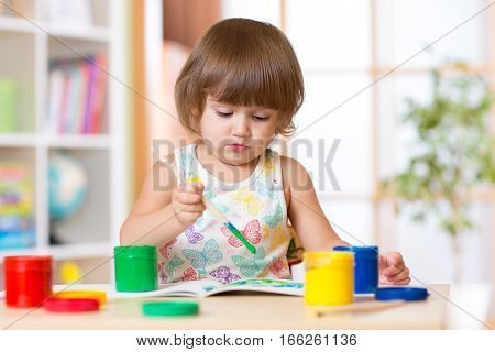 Little child girl painting with paintbrush in school. Education.