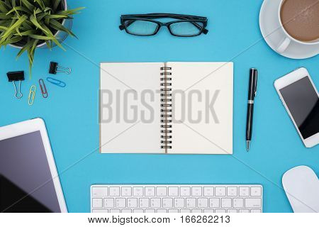 Modern blue office desk table with computer tablet other supplies eye glasses and cup of coffee Blank notebook page for input the text in the middle. Top view flat lay.
