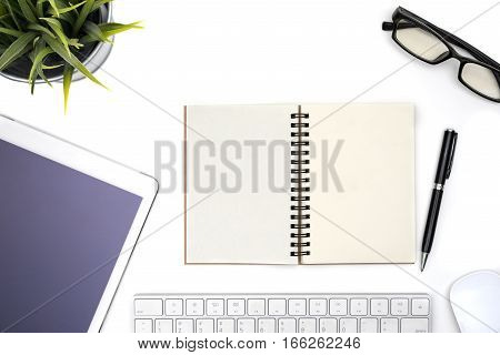 Modern white office desk table with computer tabletother supplies and eye glasses Blank notebook page for input the text in the middle. Top view flat lay.