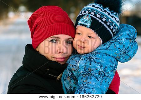 Mother with her baby cheek to cheek in a winter park