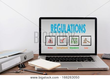 Regulations concept. Office desk with a laptop, light gray background
