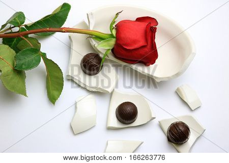 Red Rose and chocolates laying on a broken bowl