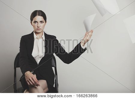 Angry Woman Elegantly Dressed Throw A Stack Of Papers To The Camera On Gray Bg Toning Photo