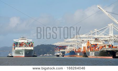 Oakland CA - January 19 2017: Multiple tugboats assisting cargo ship COSCO DEVELOPMENT to maneuver into the Port of Oakland.