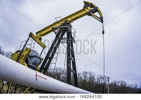 Small private yellow derrick pumps oil on the field. Development of minerals. Red arrow indicates the direction on the tube.