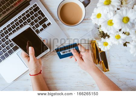 A woman using her credit card with her laptop for Online shoping with coffie and flowers