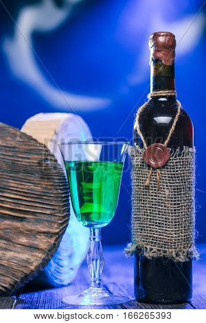 Sealed bottle of red wine and green beverage in wineglass next to rustic serving boards in mysteriuos blue light