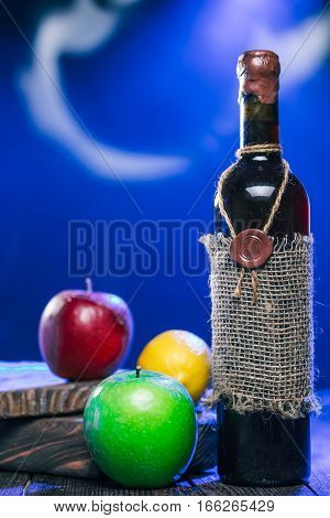 Sealed bottle of red wine, lemon and apples on rustic serving boards in mysteriuos blue light