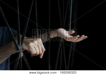 hand of woman holding cage abuse human trafficking concept with black shadow