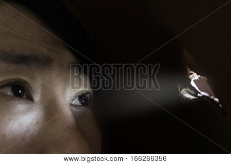 woman looking through the hole with light on black (abuse concept)