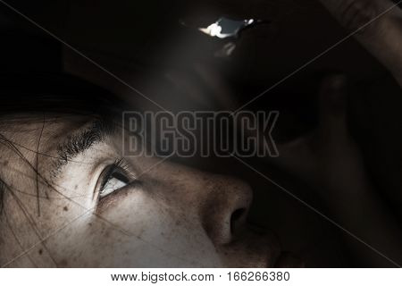 woman looking through the hole with light on black in white tone(abuse concept)