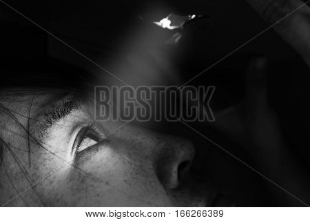 women looking through the hole with light on black in white tone(abuse concept)