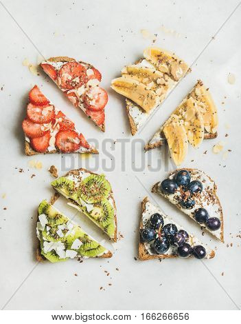 Healthy breakfast wholegrain toasts with cream cheese, various fruit, seeds and nuts. Top view, grey marble background. Clean eating, vegetarian, dieting, healthy lifestyle concept