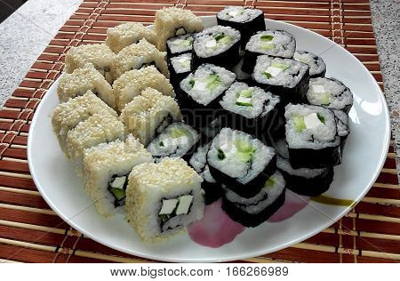 delicious and mouth-watering still life: sushi and Philadelphia roll beautifully arranged on the plate