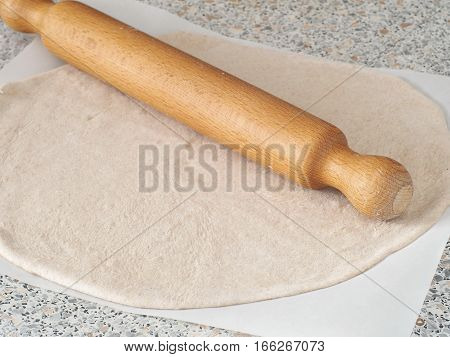 Cooking process. Preparing pizza or pie crust. Rolled out homemade wholegrain dough.