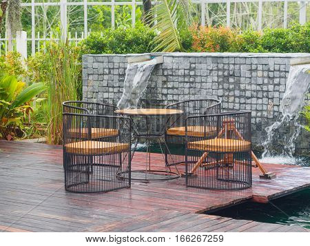 wooden and steel of Patio Furniture set on brown wooden, green grass field and water or river background