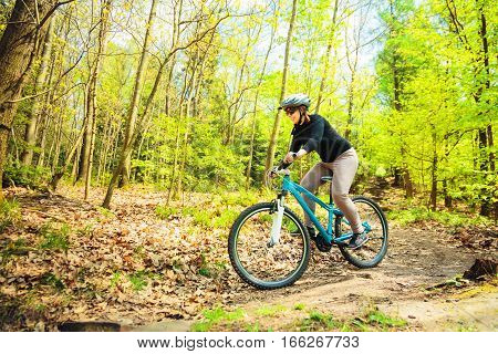 Young woman riding her mountain bike in the forest.
