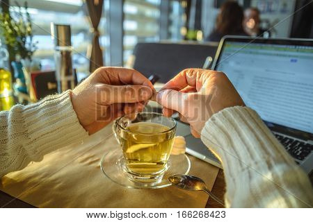 male sitiing in caffe drinking tea and working on laptop in front of window