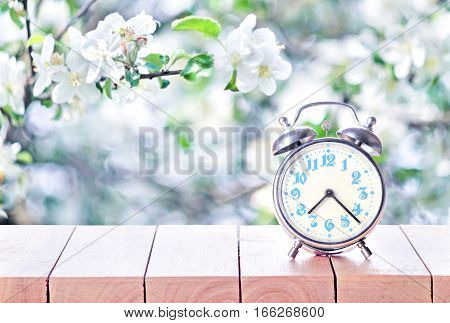 Vintage alarm clock on wooden table or bench in the spring season background. Return to spring or summer time. Fall back time. Daylight Saving Time. Switched to summer time changing clock from summertime.