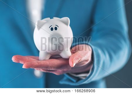 Worried and afraid piggy coin bank in hands of professional businesswoman