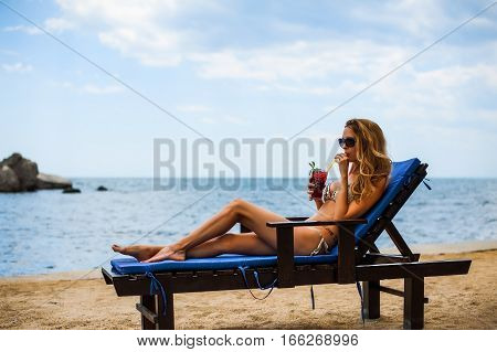 Beautiful bikini woman drink mojito cocktail with ice and mint through a straw on a beach on resort