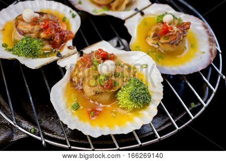 seared scallops with broccoli on black background
