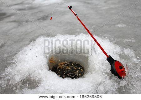 Winter fishing. Fishing rod in an ice hole