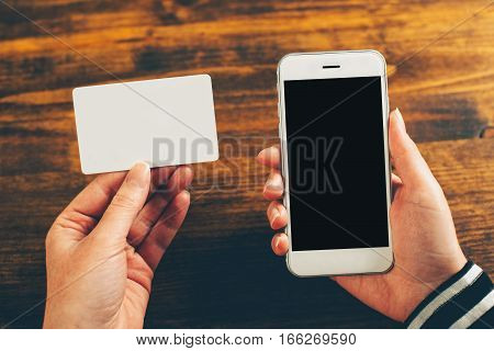 Woman holding blank business card and mobile phone with empty screen as mock up copy space for contact information and number to dial