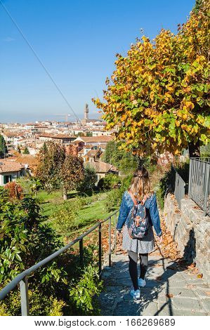 Girl Strolling Through The Rose Garden In Autumn With Panoramic View Of Florence, Tuscany, Italy.