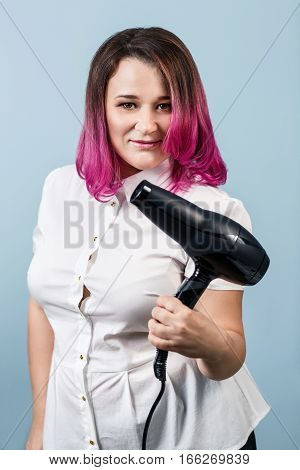 Professional hair stylist holding dryer over blue background