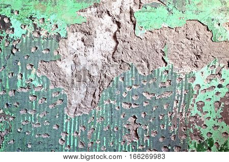 Texture of old plaster damaged brick or concrete wall. Grunge cracked concrete wall. Old vintage wall with plaster texture background. Chipped plaster on an wall weathered with cracks and scratches.