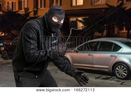 Masked Thief In Balaclava With Crowbar Wants To Rob A Car