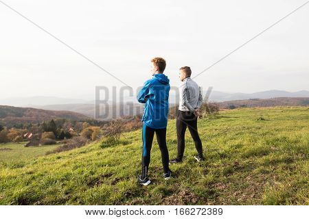 Two young handsome hipster runners in sports jackets in sunny autumn nature, resting