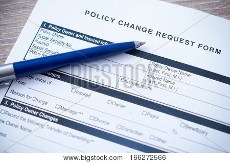 Policy change request form with blue pen shallow depth of focus field
