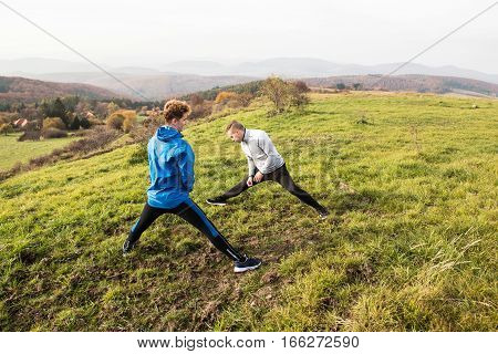 Two young handsome hipster runners in sports jackets in sunny autumn nature, resting, stretching legs