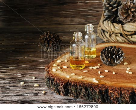 jar of oil of pine nuts, pine cones on the stone black table for spa, selective focus, space for text