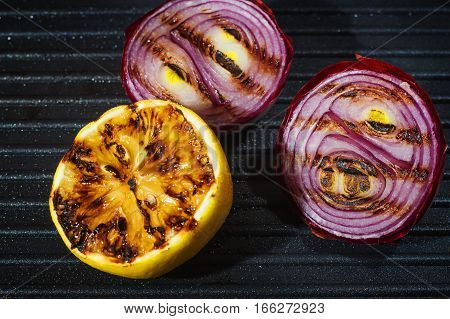 Grilled onions and lemon close up. Delicious food background. Vegetables with stripes from the grill. Grilled vegetables on pan close-up