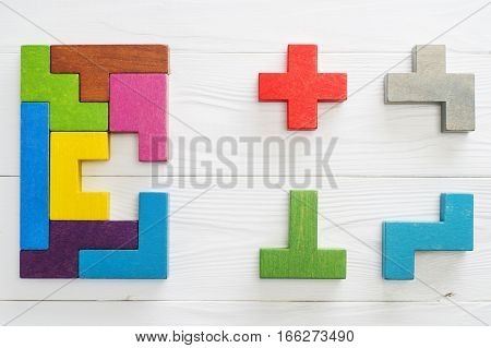 IQ test. Choose correct answer. Logical tasks composed of colorful wooden shapes top view. Children's educational logical task flat lay. Visual conundrum find the missing piece of the proposed.