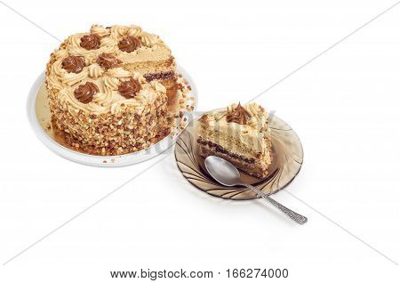 Piece of layered sponge cake decorated with butter cream caramelized condensed milk and nuts with spoon on a glass saucer and partly sliced cake on a light background