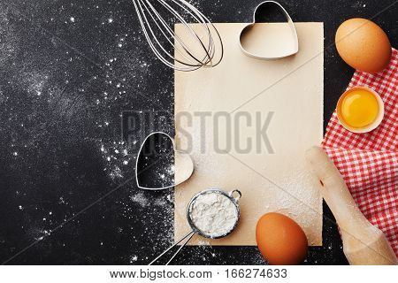 Baking background with flour rolling pin eggs paper sheet and heart shape on kitchen black table from above for Valentines day cooking. Flat lay style.