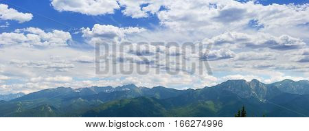 Summer panorama of massif with mountain ranges covered with spruce forest and mountain ranges with rocks and snow patches on the background of the sky with clouds