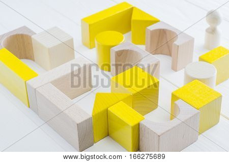 The yellow-beige maze of wooden blocks of various shapes. Man standing in front of the maze. Difficult path to find exit business concept. The concept of a strategy search for solutions.