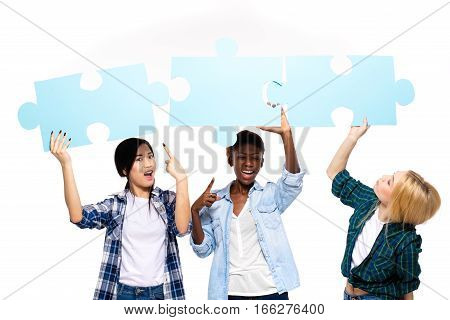 Three Friends Of Different Ethnicity With Puzzle Pieces On White