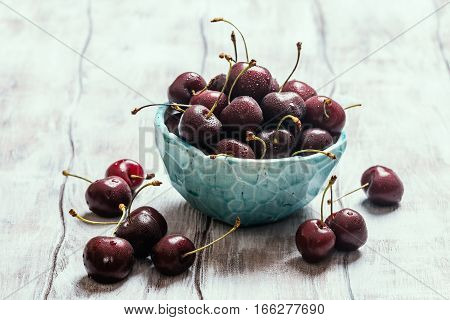 Cherries in a bowl with water drops close up on white wooden background